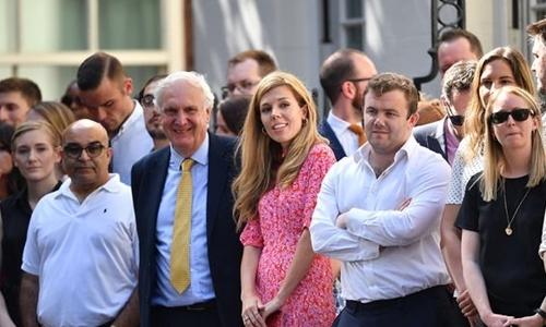 Carrie Symonds (váy hồng) đứng đợi cùng đám đông trên phố Dowing hôm 23/7 để chúc mừng bạn trai Borris Johnson. Ảnh: Reuters.