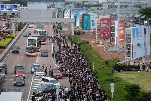 Người biểu tình và hành khách rời Sân bay Quốc tế Hong Kong chiều qua. Ảnh: Bloomberg