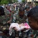 <p> Một binh sĩ Ấn Độ bế em bé sơ sinh khi sơ tán người dân tới nơi an toàn trong trận lũ lụt tại Sangli. Mưa lớn khiến đất sạt lở và gây ra lũ lụt nghiêm trọng, làm hơn 150 người thiệt mạng tại Ấn Độ, theo số liệu của chính quyền địa phương. Ảnh: <em>Reuters</em>.</p>