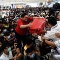 <p> Một hành khách chật vật đưa hành lý cho các nhân viên an ninh khi cố gắng tới cổng ra máy bay tại Sân bay Quốc tế Hong Kong. Người dân biểu tình tại sân bay trong 2 ngày liên tiếp, khiến hoạt động check-in bị tạm hoãn và nhiều chuyến bay ra nước ngoài phải hủy. Ảnh: <em>Getty Images.</em></p>