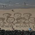 """<p> Chân dung các nguyên thủ quốc gia G7 được vẽ trên cát kèm theo dòng chữ """"Turn the tide for gender equality"""" (tạm dịch: Hãy thay đổi vì bình đẳng giới) vào ngày 23/8. Ảnh: <em>AP</em>.</p>"""