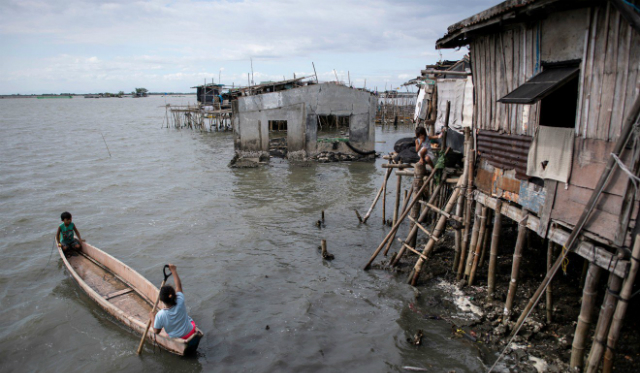 Residents use a boat to travel across the water in Sitio Pariahan, Bulacan. Photo: AFP