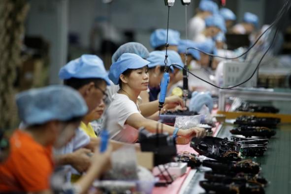 Công nhân trên dây chuyền lắp ráp robot hút bụi của công ty Matsutek ở Thâm Quyến, Trung Quốc.