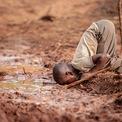 """<p class=""""Normal""""> <strong>'Khan hiếm nước' - Dharshie Wissah, Kakamega, Kenya, giải <em>Nước, bình đẳng và bền vững</em></strong></p> <p class=""""Normal""""> Một cậu bé đang phải uống nước bẩn, hậu quả của thiếu nước trong khu vực do nạn phá rừng gây ra. Thiếu nước sạch làm tăng đáng kể nguy cơ mắc các bệnh tiêu hóa như tả, sốt thương hàn và kiết lỵ, và các bệnh nhiệt đới do nước khác.</p>"""