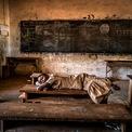 """<p class=""""Normal""""> <strong>'Mơ đẹp' - Aragon Renuncio, Burkina Faso</strong></p> <p class=""""Normal""""> Một cô gái ngủ trên chiếc bàn trong lớp học. Mưa lớn đã tăng gấp 3 ở Sahel trong 35 năm qua do sự nóng lên toàn cầu. Biến đổi khí hậu đã gây ra 70 đợt mưa lớn trong thập kỷ qua dù khu vực này cũng chịu hạn hán nghiêm trọng.</p>"""