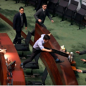 """<p class=""""Normal""""> Nhà lập pháp Au Nok-hin nhảy qua bàn để đuổi theo Trưởng đặc khu Hong Kong Carrie Lam vào ngày 17/10. Bà Lam khi đó đang rời khỏi phiên hỏi đáp với các nhà lập pháp.</p> <p class=""""Normal""""> Một ngày trước đó, Hội đồng Lập pháp Hong Kong tổ chức họp lần đầu tiên kể từ khi dự luật dẫn độ sửa đổi bị đình chỉ hồi tháng 7. Tuy nhiên, buổi họp gián đoạn nghiêm trọng khi các nhà lập pháp đối lập la ó, hô các khẩu hiệu phản đối trong lúc bà Lam phát biểu. Sau lần gián đoạn thứ nhất, bà Lam vẫn nỗ lực phát biểu, nhưng các nhà lập pháp không có dấu hiệu dừng lại, buộc Lam phải chuyển phát biểu thông qua phát video. Ảnh: <em>AP</em>.</p>"""