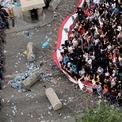 """<p class=""""Normal""""> Người biểu treo cờ lên hàng rào thép gai do cảnh sát dựng lên tại Beirut, Lebanon vào ngày 19/10. Hàng trăm nghìn người đã xuống đường bày tỏ sự giận dữ trước tình trạng kinh tế, tham nhũng và dịch vụ công tại quốc gia này. Chính phủ liên minh được cho là sẽ thông qua cải cách kinh tế, như là xóa bỏ thuế và giảm một nửa lương của các quan chức hàng đầu, để ngưng biểu tình.<br /><br /><span>Đáng chú ý, trong buổi biểu tình diễn ra vào tối 19/10, một bà mẹ và cậu con trai nhỏ vô tình bị mắc kẹt giữa đoàn người biểu tình. Để giúp cậu bé bớt sợ hãi, những người biểu tình đã hát bài """"Baby Shark"""". Ảnh: </span><em>Reuters</em><span>.</span></p>"""