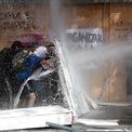 """<p class=""""Normal""""> Người biểu tình chống chính phủ bị lực lượng an ninh phun vòi rồng tại Santiago, Chile vào ngày 22/10. Tình trạng khẩn cấp được ban bố tại thủ đô Santiago vào hôm 19/10 sau khi các cuộc biểu tình nổ ra do việc tăng giá vé tàu điện ngầm. Các cuộc biểu tình lan rộng sang cả vấn đề sinh hoạt phí và bất bình đẳng.<br /><br /><span>Tổng thống Chile Sebastian Pinera ngày 26/10 kêu gọi toàn bộ Nội các của mình từ chức. Động thái này nhằm giải quyết những yêu cầu của người dân với các chính sách mới. Ông Sebastian Pinera đã thông báo một số kế hoạch nâng cao mức lương tối thiểu và lương hưu, ngừng tăng giá điện và thuế đối với người giàu cũng như tăng cường đầu tư cho chăm sóc sức khỏe. Ảnh: </span><em>Reuters</em><span>.</span></p>"""