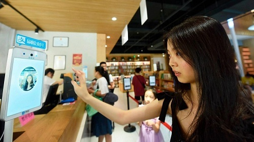 Nữ khách hàng đang sử dụng dịch vụ thanh toán bằng khuôn mặt, thông qua ứng dụng Alipay tại cửa hàng sách ở thành phố Hàng Châu, Trung Quốc. Ảnh: AP