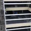 <p> Mảng tường bên ngoài đã chuyển thành màu đen. Thang cuốn lên xuống các tầng đang lắp đặt nhưng lại ngừng thi công, phủ bạt.</p>