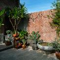 """<p class=""""Normal""""> Sân nhà được trồng nhiều cây xanh, bao quanh là bức tường gạch gợi cảm giác mộc mạc, gần gũi.</p>"""