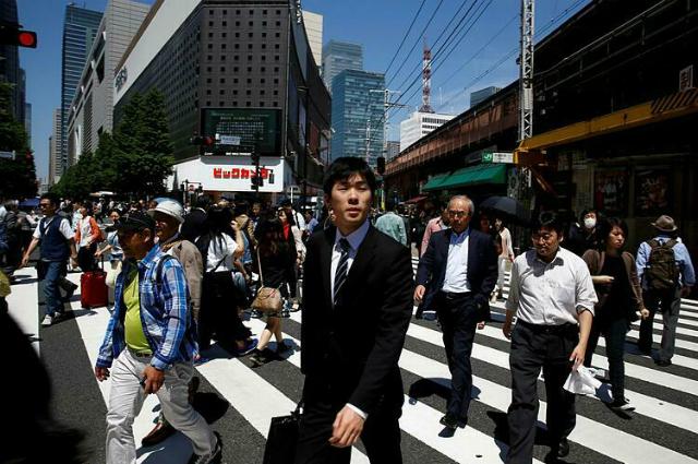 Người Nhật Bản qua đường tại một con phố ở Tokyo. Ảnh: Reuters