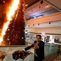 <p> Một người đang ông đang cố dập tắt ngọn lửa đang thiêu cháy một cây thông Noel tại khu trung tâm mua sắm Festival Walk ở Kowloon Tong, Hong Kong vào ngày 12/11. Người biểu tình đã đập vỡ các tấm kính của khu mua sắm này và đốt cháy các đồ trang trí Giáng Sinh tại đây. Làn sóng biểu tình kèm bạo lực tại Hong Kong dâng cao sau khi cảnh sát Hong Kong đã bắn trúng ít nhất một người biểu tình hôm 11/11 trong giờ cao điểm, giữa lúc đám đông chặn đường và kêu gọi một ngày đình công. Ảnh: <em>Reuters</em>.</p>