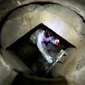 """<p class=""""Normal""""> Một người biểu tình cố gắng thoát khỏi vòng vây của cảnh sát từ bên trong Đại học Bách Khoa Hong Kong thông qua đường ống nước thải vào ngày 19/11. Tính đến ngày 19/11, có 1.100 người bị bắt và khoảng 60 - 100 người vẫn còn mắc kẹt trong khuôn viên trường đại học này. Vì cạn kiệt đồ ăn thức uống, một số tìm cách trốn bằng đường ống nước thải nhưng bị lính cứu hỏa ngăn chặn bằng việc bịt nắp hố ga. Ảnh: <em>Reuters</em>.</p>"""