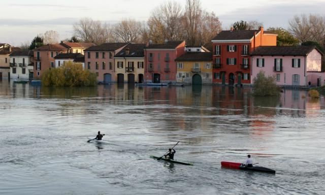 Người dân chèo thuyền về những ngôi nhà bị ngập sau khisông Ticinotại Pavia, Italy tràn bờ hôm 25/11. Ảnh: AP.