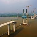 """<p class=""""Normal""""> Hiện, cây Phước Khánh đã lộ dần hình hài, các trụ cầu cao hơn 100 m sừng sững trên sông Soài Rạp. Cầu có thiết kế dây văng, tổng chiều dài 3.186 m, khẩu độ nhịp chính 300 m.</p>"""