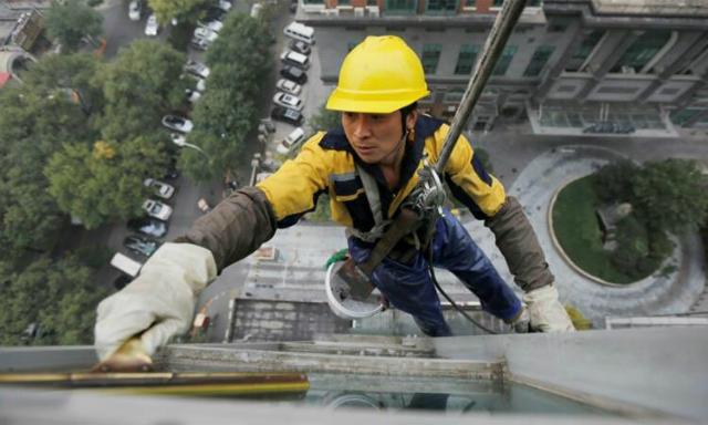 Một công nhân lau kính tòa nhà ở Bắc Kinh, Trung Quốc. Ảnh: Reuters.