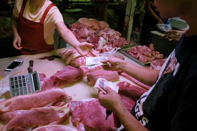 Giá thịt lợn tăng vọt kéo theo giá các mặt hàng khác tăng theo khiến người lao động Trung Quốc lao đao. Ảnh: SCMP.