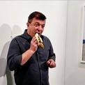 """<p> Nghệ sĩ biểu diễn David Datuna ăn tác phẩm nghệ thuật là quả chuối dán tường tại bảo tàng ở Miami Beach hôm 7/12. Quả chuối là tác phẩm nghệ thuật mang tên """"Diễn viên hài"""" của nghệ sĩ Italia Maurizio Cattelan và được bán cho một nhà sưu tập Pháp với giá 120.000 USD. Emmanuel Perrotin, người sáng lập phòng trưng bày, giải thích rằng những quả chuối là """"một biểu tượng của thương mại toàn cầu, một kiểu lộng ngữ, cũng như một hình tượng hài hước kinh điển"""". Ảnh: <em>Reuters</em>.</p>"""