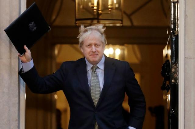 Thủ tướng Johnson bước ra khỏi Hạ viện với dự luật WAB trên tay hôm 20/12. Ảnh: AP.
