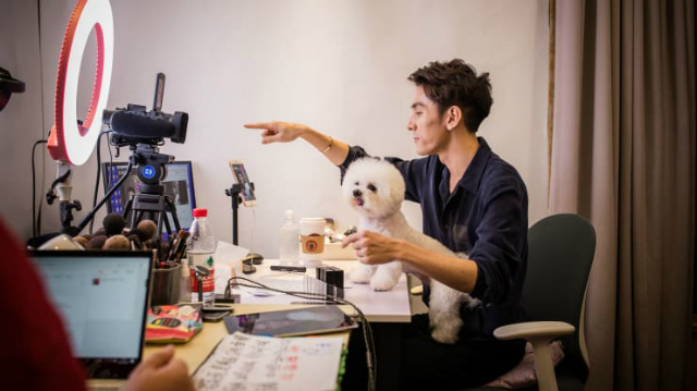 "Beauty blogger Austin Li Jiaqi speaks with a dog on his lap while livestreaming on the e-commerce platform Taobao on October 26, 2018 in Shanghai, China. The 27-year-old Li, nicknamed ""Lipstick Brother,"" is the hottest online beauty blogger in China."