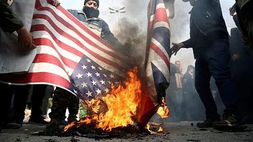 Người biểu tình tại Iran đốt cờ Mỹ và Anh sau khi tướng Qassem Soleimani bị giết. Ảnh: Reuters
