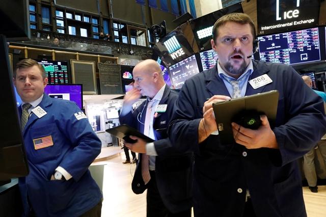 Nhân viên môi giới chứng khoán tại sàn NYSE ngày 9/1. Ảnh: Reuters.