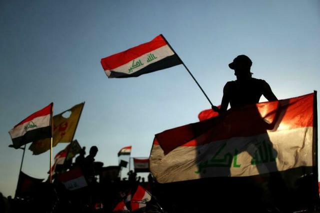 Người Iraq vẫy cờ, biểu tình chống chính phủ ở thủ đô Baghdad, tháng 11/2019. Ảnh: Reuters.