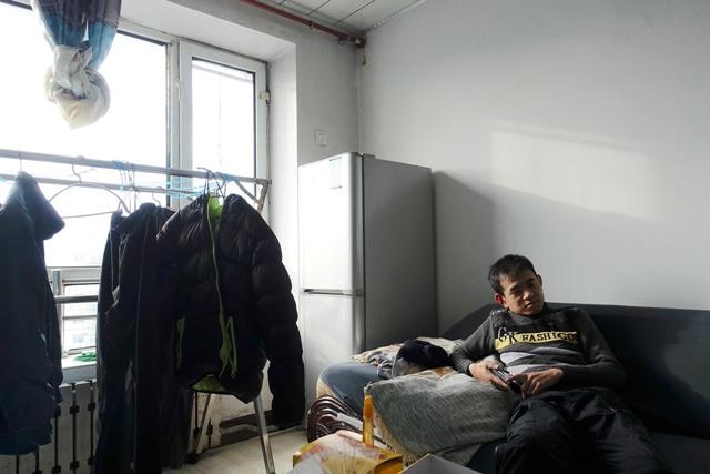 Thợ máy tàu Li Hai, 32 tuổi, trong căn hộ của anh ở Hạc Cương, Hắc Long Giang, Trung Quốc. Ảnh: Reuters.