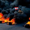 <p> Một người biểu tình chống chính phủ cầm cờ Lebanon nhảy qua hàng lốp xe đang bốc cháy để chặn đường chính ở Jal el Bib, Lebanon, vào ngày 14/1. Lebanon đang trải qua một trong những cuộc khủng hoảng kinh tế tồi tế nhất lịch sử. Làn sóng biểu tình lớn đã buộc Thủ tướng Saad Hariri phải từ chức. Ảnh: <em>AP</em>.</p>