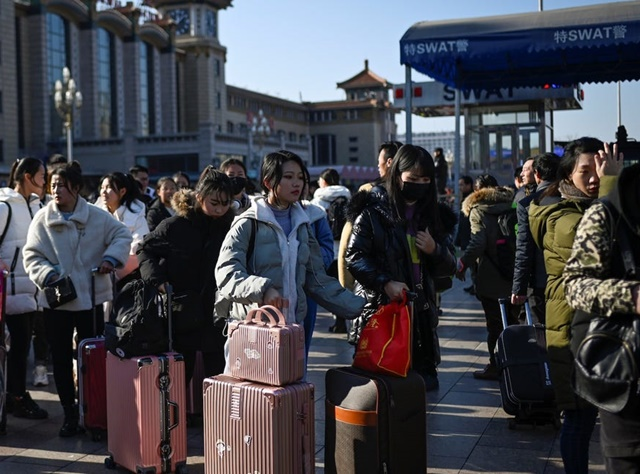 Travellers wait for their trains outside the entrance to Beijing railway station in the Chinese capital on January 10, 2020, as people begin to head for their hometowns ahead of the Lunar New Year. Wang Zhao / AFP / Getty