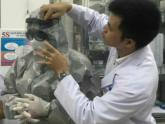 Thứ trưởng Nguyễn Trường Sơn mặc đồ bảo hộ vào phòng cách ly thăm 2 bệnh nhân đang điều trị tại Bệnh viện Chợ Rẫy tối 23/1. Ảnh: Đ.H