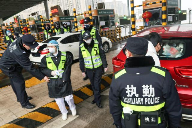 Cảnh sát kiểm tra thùng xe tại một trạm thu phí ở Xianning, gần thành phố Vũ Hán, với để rà soát có động vật hoang dã buôn bán hay không. Ảnh: Reuters.