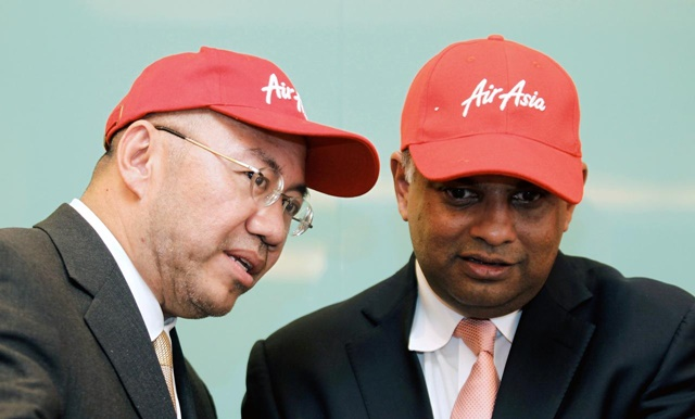 FILE PHOTO: Founder of AirAsia X Tony Fernandes (R) listens to its chairman Kamarudin Meranun during the signing ceremony for the new Airbus A330-200s in Kuala Lumpur February 28, 2011. REUTERS/Bazuki Muhammad/File Photo