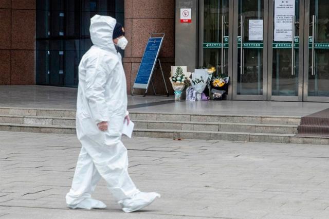 Một nhân viên y tế đi qua nơi đặt hoa tưởng niệm bác sĩ Lý Văn Lượng ở Vũ Hánngày 7/2. Ảnh: AFP.