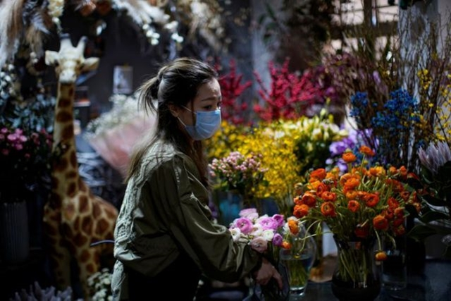 Florist Wang Haiyan, 41, works on flowers inside her shop as the country is hit by an outbreak of the new coronavirus, in Shanghai, China February 5, 2020. REUTERS/Aly Song