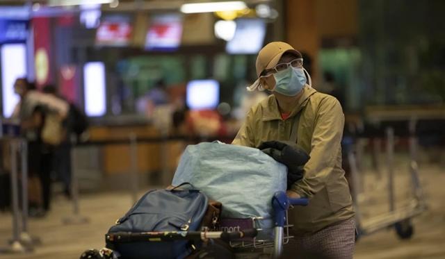 Du khách đeo khẩu trang tại sân bay Changi, Singapore. Ảnh: EPA.