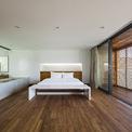 """<p> Một phòng ngủ trong chiếc """"hộp gỗ"""" được thiết kế khá đơn giản, không nhiều đồ đạc với tông màu trầm của sàn nhà, tủ quần áo... xen kẽ màu trắng của trần nhà, ga đệm.</p>"""