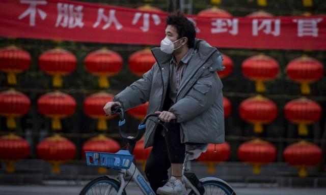 Một người dân đeo khẩu trang đạp xe ở Vũ Hán, thủ phủ tỉnh Hồ Bắc hôm 1/3. Ảnh: AFP.