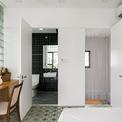 """<p class=""""Normal""""> Khác với tầng 2, tầng 3 không sử dụng lớp cửa kính lá chuối để ngăn cách phòng ngủ với nhà vệ sinh. Thay vào đó, một bức tường màu trắng mỏng được dùng để phân chia không gian.</p>"""