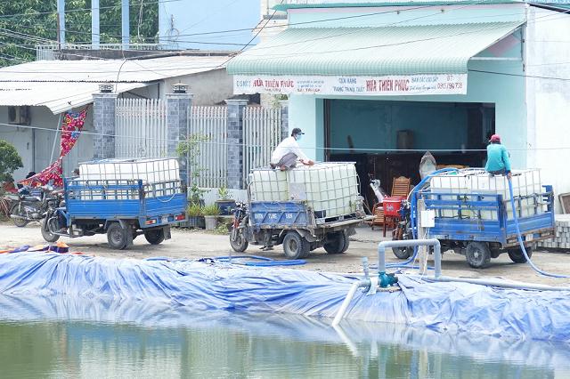 Người dân xã Thạch Phú Đông (huyện Bình Đại, tỉnh Bến Tre) dùng xe máy chở nước ngọt về sinh hoạt