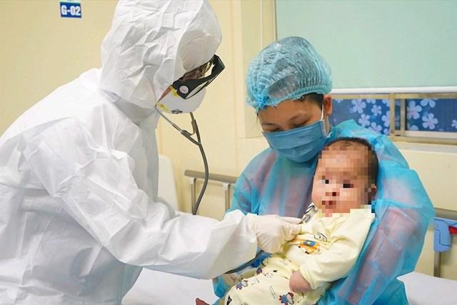 Bác sĩ khám cho em bé 3 tháng tuổi mắc bệnh COVID-19. Ảnh: Tuấn Dũng.