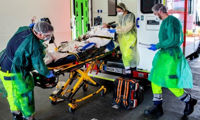 Nhân viên y tế chuyển bệnh nhân Covid-19 từ Italy tới bệnh viện ở phía tây nước Đức hôm 28/3. Ảnh: AFP.