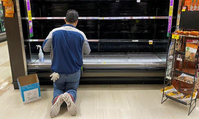 Nhân viên siêu thịRalphs vệ sinh kệ trứng trống rỗng ởLos Angeles hôm 15/3. Ảnh: Reuters