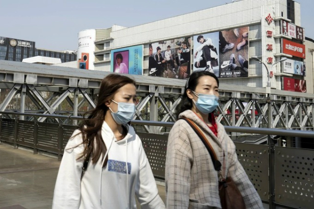 Người dân đeo khẩu trang đi qua một trung tâm thương mại ở Trung Quốc. Ảnh: Bloomberg