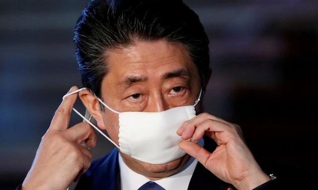 Thủ tướng Nhật Shinzo Abe điều chỉnh khẩu trang khi trò chuyện với truyền thông về phản ứng của Nhật với Covid-19 tại Tokyo hôm 6/4. Ảnh: Reuters.