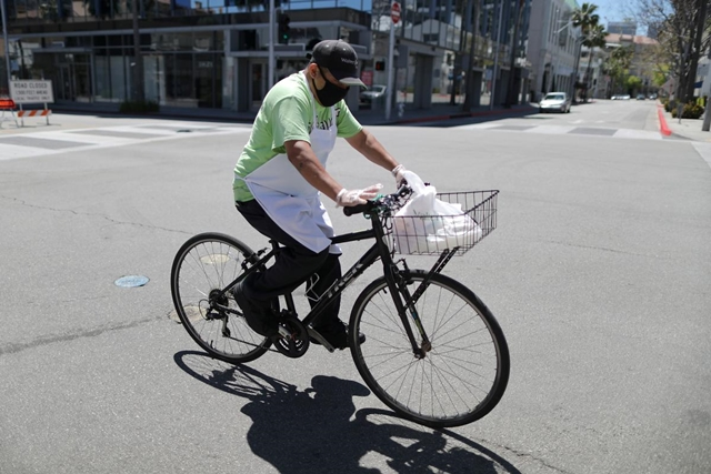 A food delivery driver cycles on an empty road as the global outbreak of the coronavirus disease (COVID-19) continues, in Beverly Hills, California, U.S., April 15, 2020. REUTERS/Lucy Nicholson