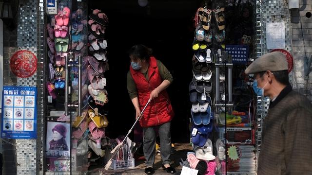 Một người lau dọn lối ra vào cửa hàng ở Bắc Kinh, Trung Quốc. ngày 17/4. Ảnh: Reuters.