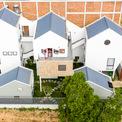 """<p class=""""Normal""""> Nhà được xây trên khu đất rộng 500 m2. Cổng nhà nằm trên tuyến đường chính trong khi ba mặt còn lại giáp với những khoảng đất trống.</p> <p class=""""Normal""""> Phía Tây ngôi nhà là bức tường cao 15 m, được xây dựng từ các khối breeze blocks nhằm ngăn chặn các tác động từ mặt trời.</p>"""