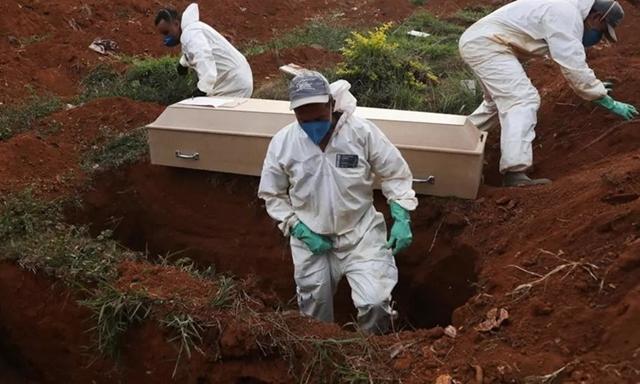 Những phu đào mộ mặc đồ bảo hộ chuẩn bị chôn cất quan tài một nạn nhân Covid-19 trong tang lễ không có người thân ở Sao Paolo, Brazil hôm 22/5. Ảnh: AFP.